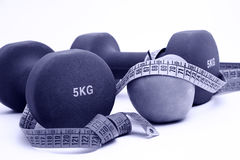 Dumbbells and measure tape Stock Images