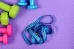 Dumbbells and measure tape in cyan color on purple texture. Background. Healthy shape and sport concept. Shaping and fitness equipment. Barbells in pink, green stock photo