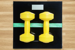 Dumbbells with measurement tools on wooden table Stock Photo
