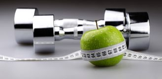 Dumbbells with measuring tape and apple for diet Stock Photos