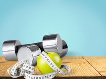 Dumbbells with measuring tape and apple for diet Royalty Free Stock Photos