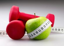 Dumbbells with measuring tape and apple for diet Stock Image