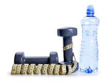 Dumbbells with measuring tape and bottle with drinking water isolated on white background. Stock Images