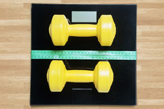 Dumbbells and measuring tape on the scales Stock Photos