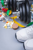 Dumbbells with measuring tape, trainers, pills and bottle of chilling water Royalty Free Stock Photo