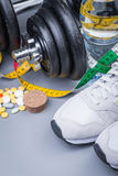 Dumbbells with measuring tape, trainers, pills and bottle of chilling water Stock Photo