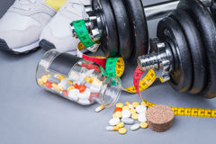 Dumbbells with measuring tape, trainers, pills and bottle of chilling water Stock Photos