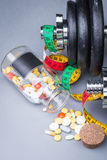 Dumbbells with measuring tape, trainers, pills and bottle of chilling water Stock Images