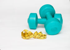 Dumbbells and measuring tape on white background Royalty Free Stock Image