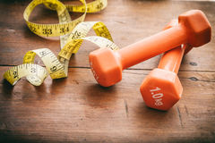 Dumbbells and measuring tape Stock Photography