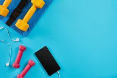 Dumbbells and mobile phone on blue background. Top view. Fitness, sport and healthy lifestyle concept. stock photos