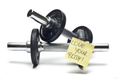 Dumbbells with note. Free weights with a note in front of white Royalty Free Stock Image