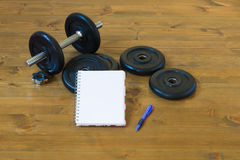 Dumbbells with a notebook to record results. Dismantled dumbbell with a notebook to record results Stock Images