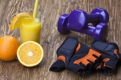 Dumbbells, orange juice, fitness gloves and measuring tape Stock Images