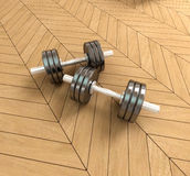 Dumbbells on a parquet floor Stock Images