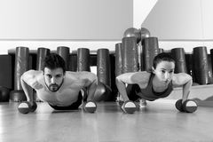 Dumbbells push-ups couple at fitness gym Stock Image
