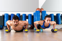 Dumbbells push-ups couple at fitness gym. Dumbbells push-ups pushups couple at fitness gym workout royalty free stock photography