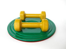 Dumbbells and the roll disk. A couple of yellow dumbbells on the green roll disk Stock Photo