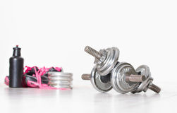 Dumbbells with sneakers and bottle Stock Photos
