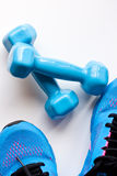 Dumbbells and sport shoes Stock Photos