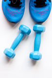 Dumbbells and sport shoes Stock Photography