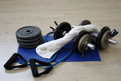 Dumbbells and stacked weights on a Gym floor. With white towel Royalty Free Stock Photo