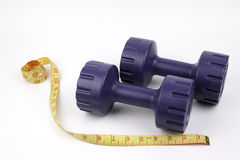 Dumbbells and tailoring meter on white background Stock Photo