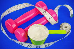 Dumbbells with tape measure and whey powder Royalty Free Stock Photo