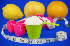 Dumbbells with tape measure,whey powder and fruits on blue Royalty Free Stock Photos