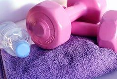 Dumbbells on towel. Pink dumbbells and water-bottle on violet towel stock photos