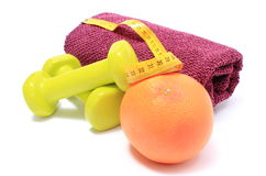 Dumbbells and towel for using in fitness, fresh fruit with tape measure Royalty Free Stock Photo