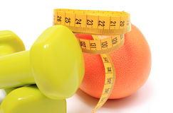 Dumbbells for using in fitness, fresh fruit and tape measure Royalty Free Stock Photography