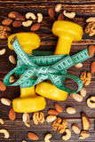 Dumbbells and variety of nuts. stock photos