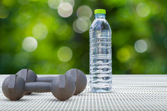 Dumbbells and water bottle side view on aluminium floor on blurred bokeh background Royalty Free Stock Photo