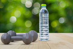 Dumbbells and water bottle side view on aluminium floor on blurred bokeh background Stock Images