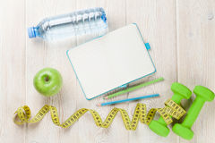 Dumbbells, water and notepad Royalty Free Stock Image