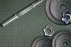 Dumbbells and weights are lying on the floor in the gym. Barbell set and gym equipment. Metal loads in the fitness club royalty free stock image