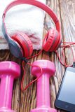 Dumbbells With Towel On Wooden Background, Concept Preparing To Fitness Sports Equipment Top View. Headphones And Phone. Music In Royalty Free Stock Image