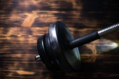 Dumbbells on a wooden dark background. Concept of playing sports Stock Images