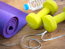 Dumbbells,yoga mat, bottle of water and measuring tape for fitne Stock Images
