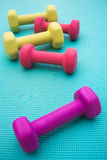 Dumbbells on a Yoga Mat. Five colorful dumbbells scattered on a bright blue yoga mat Stock Photos