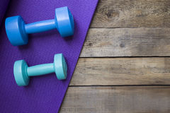 Dumbbells and yoga mat. On wood table Stock Images