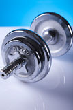Dumbell. Iron, shiny dumbell on the blue background Royalty Free Stock Images