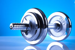 Dumbell. Iron dumbell on blue background Royalty Free Stock Images