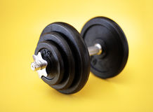 Dumbell. Metallic dumbell on yellow surface. Very short depth-of-field Royalty Free Stock Image