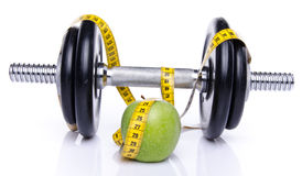 Dumbell and an apple with a tape measure. Isolated on white Royalty Free Stock Photo