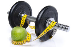 Dumbell and an apple with a tape measure Stock Photo