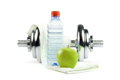 Dumbell, bottle, towel and apple. Metal dumbell with green apple, bottle of water and towel. Isolated on white Royalty Free Stock Images