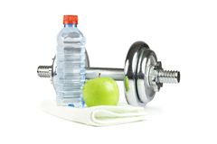 Dumbell, bottle, towel and green apple. Metal dumbell with green apple, bottle of water and towel Royalty Free Stock Images