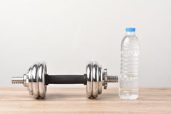 Dumbell. And water pace on wood background Royalty Free Stock Photo